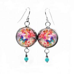 Boucles d'oreilles fantaisie pendantes avec le thème Summertime Papillon turquoise sur fond de feuilles rouges
