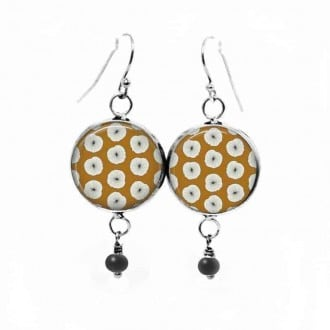 Dangle earrings with a white floral pattern on a mustard background