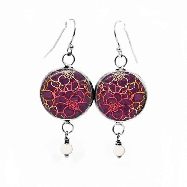 Boucles d'oreilles pendantes avec un motif floral sur fond prune
