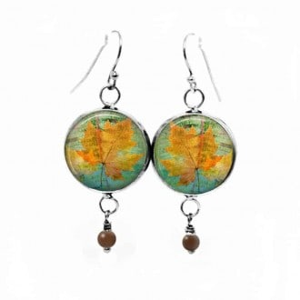 Dangle earrings with a herbarium yellow leaf theme on green background