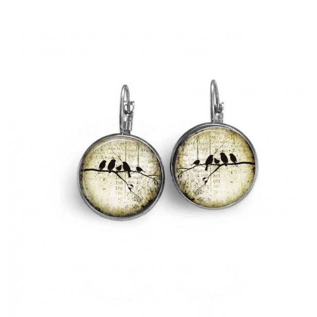 French sleeper style earrings with a bird family on a branch on a beige  background