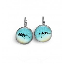 French sleeper style earrings with a bird family on a branch on a turquoise blue background