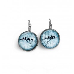 French sleeper style earrings with a bird family on a branch on a blue background