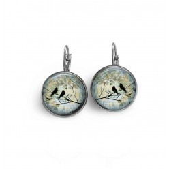 Lever-back style earrings with two birds on a branch on a teal background