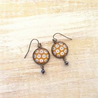 Boucles d'oreilles pendantes avec le motif fleurs blanches sur fond moutarde
