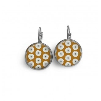 French wire lever-back earrings with white floral pattern on a mustard background