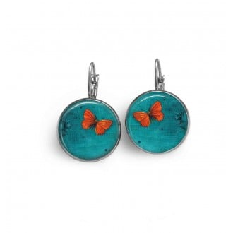 Sleeper earrings with an orange butterfly theme on a deep turquoise background