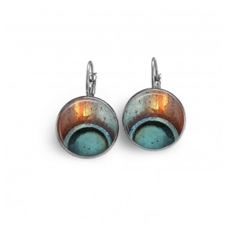 Lever-back earrings with a turquoise blue and rust abstract circle pattern