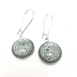 Boucles d'oreilles pendantes avec un thème abstrait cercles en argent sur fond vert forêt