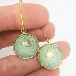 Gold dangle earrings with a queen annes lace theme on a watercolor green background