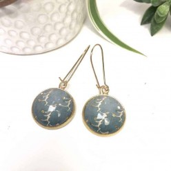 Dangle earrings with a teal blue background and gold touches