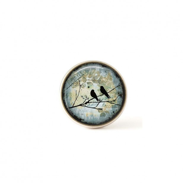 Interchangeable clip on buttons birds on a branch teal background