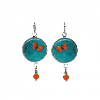 Beaded dangle earrings with an orange butterfly theme on a deep turquoise background