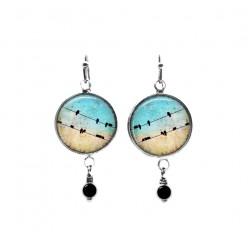 Boucles d'oreilles pendantes ornées de perles sur le thème des oiseaux sur un fil et du ciel turquoise